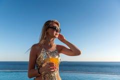 La muchacha en un traje de baño costoso con un cóctel en sus manos pasa sus vacaciones cerca de la piscina en el centro turístico fotos de archivo