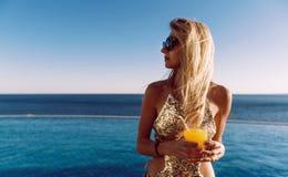 La muchacha en un traje de baño costoso con un cóctel en sus manos pasa sus vacaciones cerca de la piscina en el centro turístico fotografía de archivo