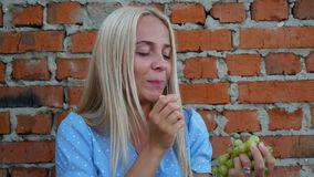 La muchacha en un vestido azul come las uvas almacen de metraje de vídeo