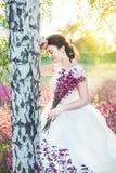 La muchacha en un vestido blanco con un ramo en un campo del verano en la puesta del sol se coloca cerca del abedul Imágenes de archivo libres de regalías
