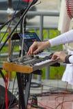 La muchacha en un vestido blanco juega en un sintetizador eléctrico foto de archivo libre de regalías