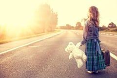 La muchacha en un vestido con una maleta Foto de archivo libre de regalías