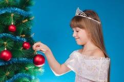 La muchacha en un vestido cuelga para arriba un juguete del Año Nuevo en un abeto y Foto de archivo libre de regalías