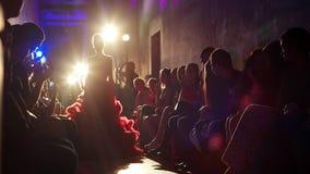 La muchacha en un vestido de bola rojo elegante va hacia las luces