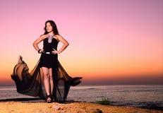 La muchacha en un vestido de noche en la costa fotos de archivo