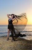 La muchacha en un vestido de noche en la costa Foto de archivo libre de regalías