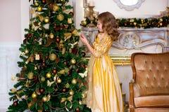 La muchacha en un vestido del oro en la Navidad Foto de archivo libre de regalías