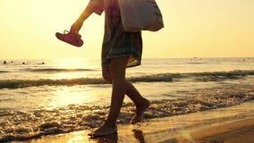La muchacha en un vestido está caminando a lo largo de la playa del mar contra la puesta del sol metrajes