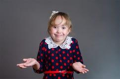 La muchacha en un vestido hace un gesto desamparado en los lados y el SM Fotos de archivo