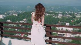 La muchacha en un vestido hermoso corre a través de la terraza sobre la ciudad metrajes
