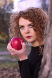 La muchacha en un vestido negro con la manzana roja Fotografía de archivo