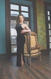 La muchacha en un vestido negro se coloca cerca del sofá Foto de archivo libre de regalías
