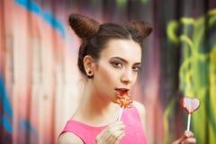La muchacha en un vestido rosado con el caramelo en un fondo adornado de la pared de la pintada Foto de archivo