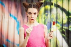 La muchacha en un vestido rosado con el caramelo en un fondo adornado de la pared de la pintada Fotografía de archivo