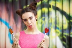 La muchacha en un vestido rosado con el caramelo en un fondo adornado de la pared de la pintada Fotos de archivo