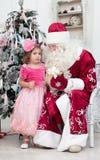 La muchacha en un vestido rosado habla con el Saint Nicolas Fotografía de archivo libre de regalías