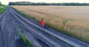 La muchacha en un vestido va con la bici a lo largo de campos del trigo Tiroteo en el abejón Paisaje hermoso de una altura metrajes