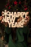 La muchacha en un vestido verde cerca de un árbol del Año Nuevo Foto de archivo libre de regalías