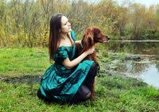 La muchacha en un vestido verde con el perro de aguas del escocés del perro Foto de archivo libre de regalías