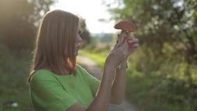 La muchacha en un vestido verde mira el boleto del anaranjado-casquillo que se coloca en el bosque metrajes