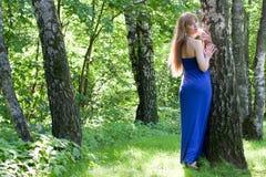 La muchacha en una alineada azul marino cerca de un abedul Imagen de archivo