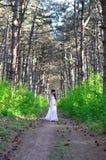 La muchacha en una alineada blanca va en la madera Fotografía de archivo