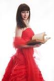 La muchacha en una alineada roja con el libro viejo Imagenes de archivo