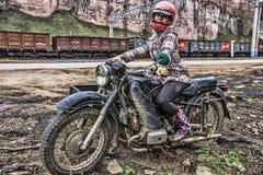 La muchacha en una bici pesada con un coche lateral vino para hacer compras, sta del tren Foto de archivo