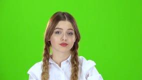 La muchacha en una blusa blanca y coletas muestra una pantalla del verde del puño almacen de video