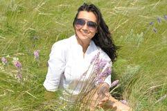 La muchacha en una blusa blanca y las gafas de sol en verano colocan Foto de archivo