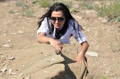 La muchacha en una blusa blanca y vidrios sube en la roca Foto de archivo