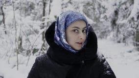 La muchacha en una bufanda azul en el bosque del invierno muestra emociones simuladas almacen de video
