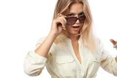 La muchacha en una camisa amarilla corrige las gafas de sol Fotografía de archivo libre de regalías