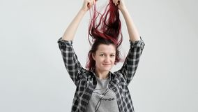 La muchacha en una camisa gris de la tela escocesa en un fondo blanco con el pelo rojo te?ido metrajes