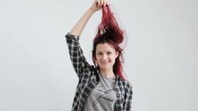 La muchacha en una camisa gris de la tela escocesa en un fondo blanco con el pelo rojo te?ido almacen de video