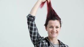 La muchacha en una camisa gris de la tela escocesa en un fondo blanco con el pelo rojo te?ido almacen de metraje de vídeo