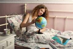 La muchacha en una camiseta blanca, sentándose en una cama Foto de archivo