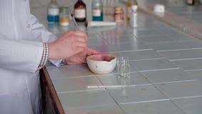 La muchacha en una capa blanca revuelve la solución química en un plato especial almacen de video
