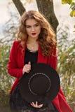 La muchacha en una capa del rojo sostiene un sombrero negro en sus manos se sienta en un árbol por el lago Fotografía de archivo libre de regalías