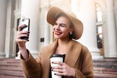La muchacha en una capa marrón un sombrero marrón es que camina y de presentación en los interiores de la ciudad La muchacha está Fotos de archivo