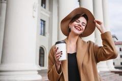 La muchacha en una capa marrón un sombrero marrón es que camina y de presentación en los interiores de la ciudad La muchacha está Imágenes de archivo libres de regalías