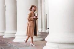 La muchacha en una capa marrón un sombrero marrón es que camina y de presentación en los interiores de la ciudad La muchacha está Foto de archivo libre de regalías