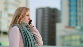La muchacha en una capa rosada con el teléfono camina en una ciudad moderna fondo de rascacielos almacen de video