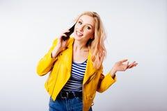 La muchacha en una chaqueta amarilla brillante hace un selfie para las redes sociales en el smartphone fotografía de archivo