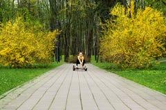 La muchacha en una chaqueta del oro realiza balanzas de los ejercicios de los deportes en un hoverboard fotos de archivo