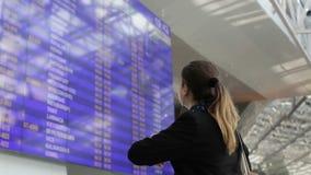 La muchacha en una chaqueta negra está mirando el horario el aeropuerto almacen de video