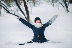la muchacha en una chaqueta negra y un sombrero negro se sienta en una secuencia en la nieve y lanza nieve Niño feliz después del Fotos de archivo