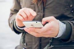 La muchacha en una chaqueta verde utiliza un smartphone mientras que camina en el fondo del mar Fotos de archivo libres de regalías