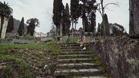 La muchacha en una falda rayada sube para arriba las escaleras rocosas demasiado grandes para su edad con el musgo contra un fond metrajes
