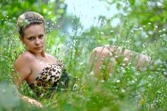 La muchacha en una hierba Foto de archivo libre de regalías